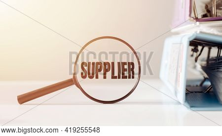 Magnifying Glass With The Word Supplier On Office Table.