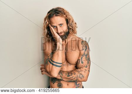 Handsome man with beard and long hair standing shirtless showing tattoos thinking looking tired and bored with depression problems with crossed arms.