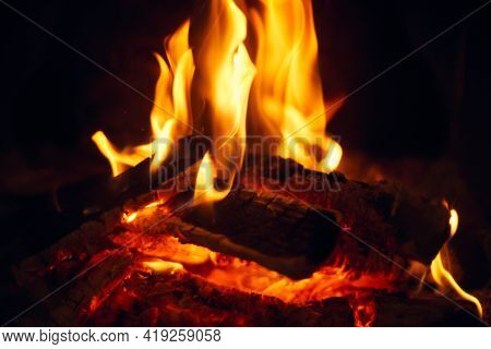 A Fire Burns In A Fireplace, Fire To Keep Warm. Logs Burning In