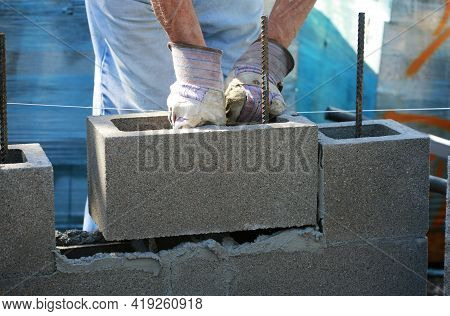 Construction Site: Building Wall Of Concrete Block. Mason Is Laying Concrete Blocks