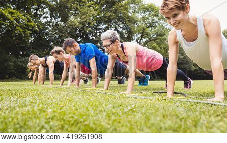 Fitness group practising push-ups in park