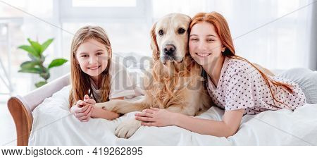 Two sisters lying in the bed with golden retriever dog in the morning time and looking at the camera. Girls with pet staying at home. Beautiful portrait of friendship between human and animal