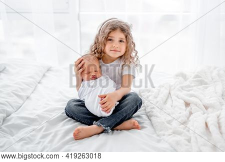 Cute little curly hair girl sitting on the bed and holding newborn baby. Beautiful portrait of sister and infant child together at home. Happy family moments with children