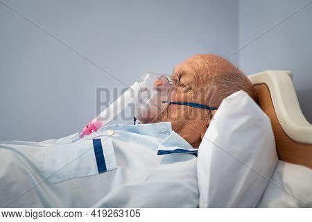 Ill senior man lying in hospital bed while wearing an oxygen mask for undergoing treatment. Sick old patient resting in hospital breathing in oxygen mask in intensive care with copy space.