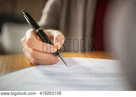 Close up of woman hand signing legal documents. Businesswoman signing a financial contract. Close up of hands of young woman closes a deal.