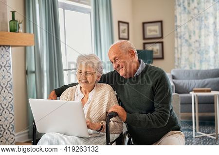 Disabled old woman on wheelchair using laptop with husband during a visit at care facility. Elderly woman wearing spectacles sitting on wheelchair with husband for a video call. Happy senior couple.