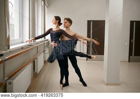 Female and male ballet dancers dancing at barre