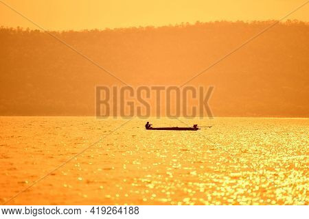 Asia Fisherman On Wooden Boat Sunset Or Sunrise In The River - Silhouette Fisherman Boat With Mounta