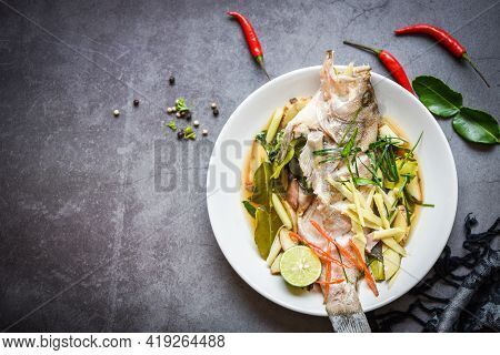 Steamed Fish On White Plate With Ginger Chili Herb And Spices Lemon Lime On Dark Background, Steamed