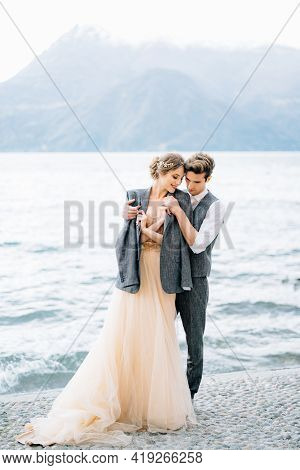 Groom Threw A Jacket Over The Shoulders Of Bride Hugging Her On The Embankment Of Lake Como Near The