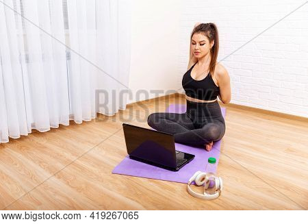 Beautiful Young Woman Practicing Yoga. Young Woman Doing Yoga Exercise Indoors At Home, Meditating.