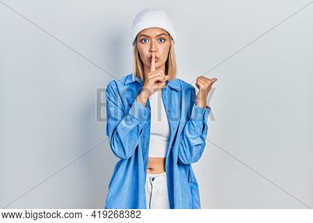 Beautiful blonde woman wearing wool hat asking to be quiet with finger on lips pointing with hand to the side. silence and secret concept.