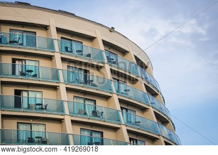 A Residential Building With Flat, Identical Balconies With Ripped Air Conditioners And  Glass. Balco