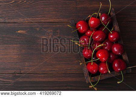 Cherry, Water Drops On Wooden Box On Dark Wooden Table. Ripe Ripe Cherries. Sweet Red Cherries. Top