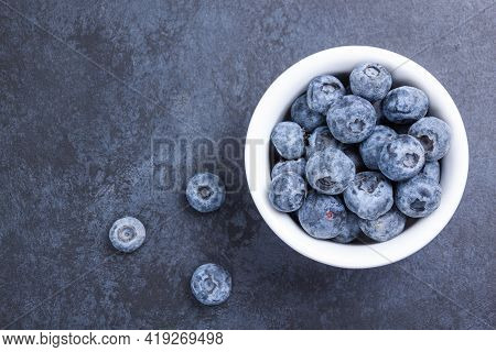 Fresh Blueberry In White Bowl On Black Background. Organic Fruit Berry Of Bilberry. Blueberry Antiox