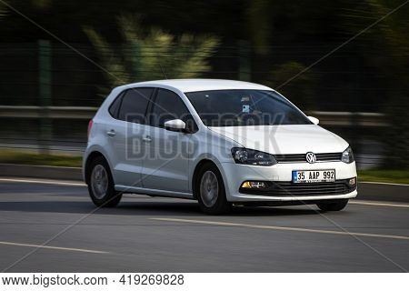 Alanya, Turkey - April 16 2021:   White Volkswagen Polo  Is Driving Fast On The Street On A Warm Sum