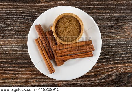 Cinnamon Sticks And Bamboo Bowl With Ground Cinnamon In White Plate On Dark Wooden Table. Top View