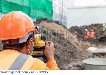 A Surveyor Is Working With Construction Workers.