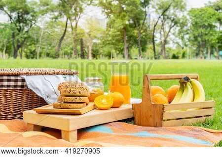 Summer Picnic With Fruits,orange,banana And Bread, Jam. Picnic In The Park With Orange Juice And Pic