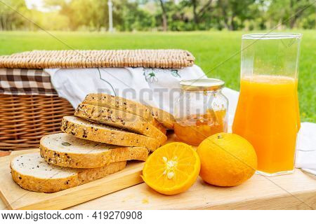 Summer Picnic With Fruits And Bread And Jam. Picnic In The Park With Orange Juice And Picnic Basket.