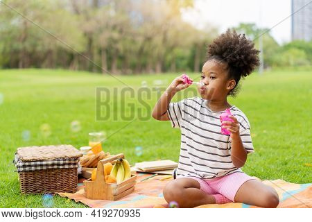 Happy Little African American Curly Hair Girl Blowing Soap Bubbles Playing Alone In The Park, Black