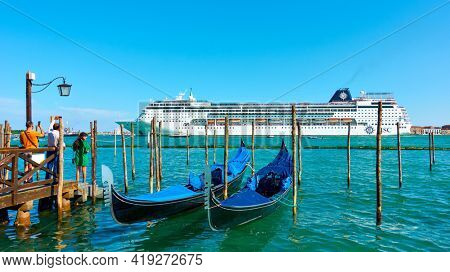Venice, Italy - June 16, 2018: Huge cruise ship passing venetian lagoon and watching people on pier in Venice