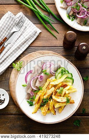 Pickled Herring Fillet With Onion And Fried Potato On Plate