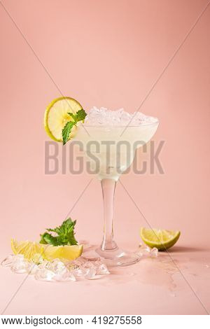 Cocktail Margarita Garnished With Lime And Mint On Pink Background