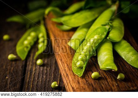 Pods Of Green Peas On A Old Wooden Background Close Up, Soft Focus