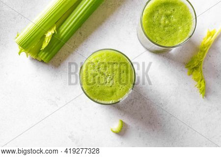 Celery Juice In Glasses. Fresh Squeezed Detox Green Juice And Bunch Of Organic Celery On White Table