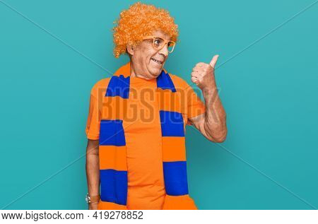 Senior hispanic man football hooligan cheering game smiling with happy face looking and pointing to the side with thumb up.