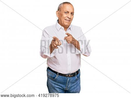 Handsome senior man wearing elegant white shirt pointing fingers to camera with happy and funny face. good energy and vibes.