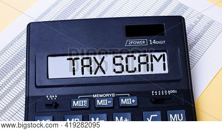 A Calculator Labeled Tax Scam Is On The Table Near The Report. Financial Concept