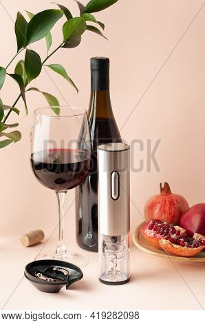 Electric Corkscrew Made Of Metal. Nearby Is A Corkscrew Stand. Cut Pomegranate On A Plate. Bottle An