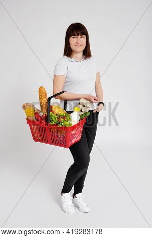 Full Length Portrait Of Young Woman With Shopping Basket Full Of Products Over White Background