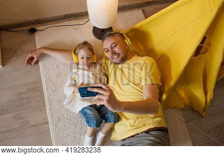 A Father And His Little Daughter Are Lying On The Floor In Yellow Headphones And Listening To Music