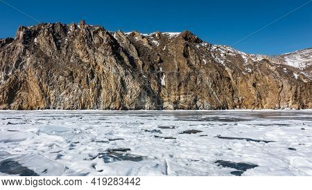 A Picturesque Mountain Range, Devoid Of Vegetation And Covered With Snow, Rises Above The Icy Lake.