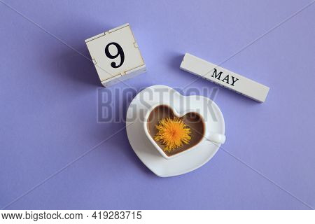 Calendar For May 9: A Cube With The Number 9, The Name Of The Month Of May In English, A Cup Of Coff