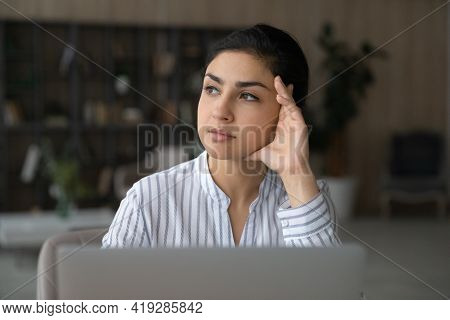 Close Up Thoughtful Indian Woman Distracted From Laptop, Pondering Strategy