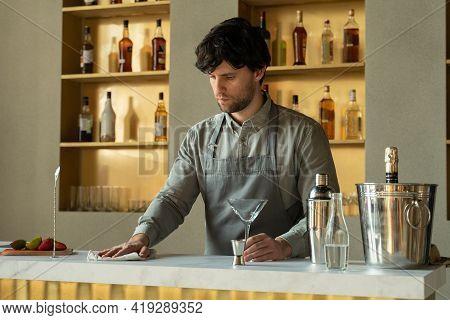 Man Bartender Standing At Bar Counter Wiping Table Cheerful. Bartender In The Workplace