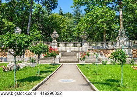 Old Stone Stairway With Columns And Bowls And Ornaments Among Flowers And Trees. It's Part Of Massan