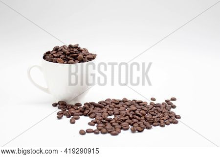Roasted Coffee Beans In White Cup With Roasted Coffee Beans On White Background.