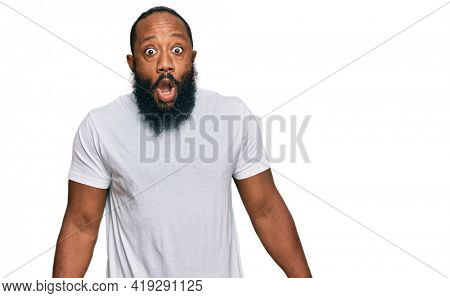 Young african american man wearing casual white tshirt afraid and shocked with surprise expression, fear and excited face.