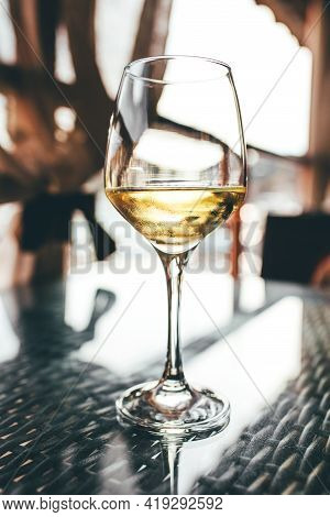 A Glass Of White Wine On The Table.