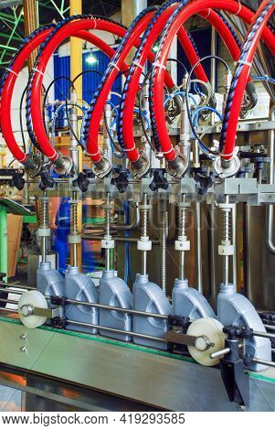 The bottles are transferred on the conveyor belt system. Industrial machine for automotive lubricating oil factory. Industrial and technology concept.
