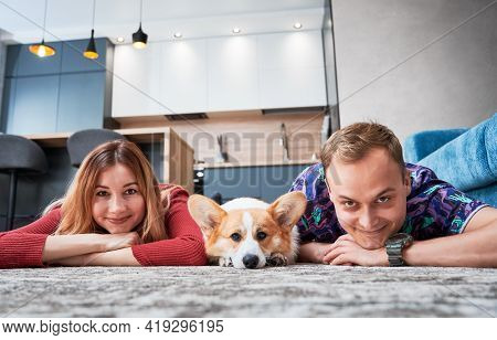 Cheerful Man And Woman Looking At Camera And Smiling While Lying On The Floor With Adorable Corgi. H
