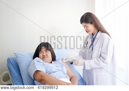 Beautiful Asian Female Doctor Injecting An Injection To An Obese Woman Who Is Lying In Bed Treat Dis