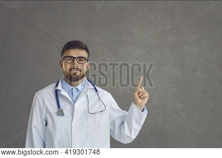 Male Doctor With Raised Finger Give Some Advice Or Suggestion On Studio Space