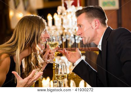 Couple have a quarrel on a romantic date in a fine dining restaurant they are angry and yelling, a large chandelier is in Background
