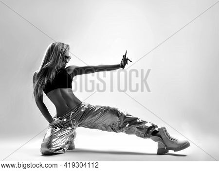 Black And White. Sporty Woman, Dancer In Silver Pants And Black Top Is Sitting On The Floor With One